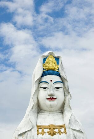 Guanyin statue with a white clouds background photo