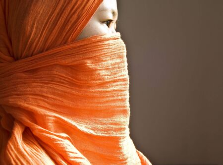 purdah: Close-up of a islamic woman covered with a orange veil