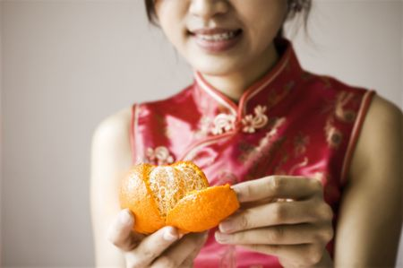 cheongsam: Oriental girl with cheongsam costume peeling a tangerine Stock Photo