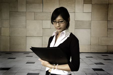 buiding: Young women holding a file, buiding as  background