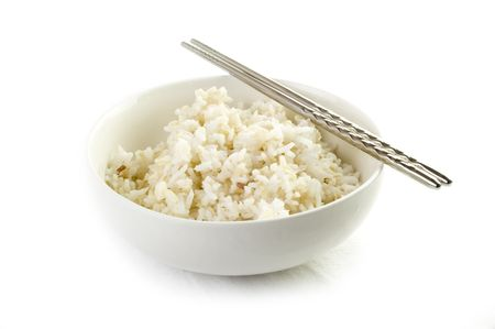 brown rice: A bowl of cooked brown rice, in an Asian style bowl, with chopsticks isolated on white