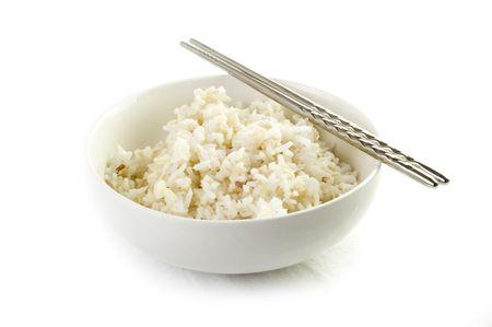 arroz chino: Un plato de arroz integral cocido, en un cuenco de estilo asi�tico, con palillos aislados en blanco  Foto de archivo