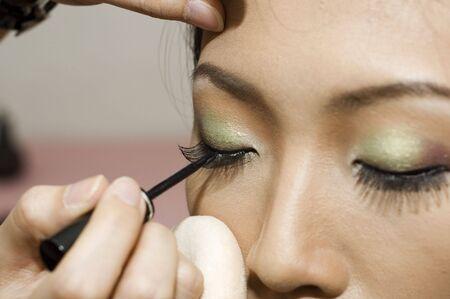 mujer maquillandose: Una joven mujer aplicar maquillaje  Foto de archivo