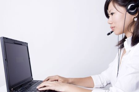 Asian consultants with headsets working on laptop computer on grey background. Stock Photo - 3795000