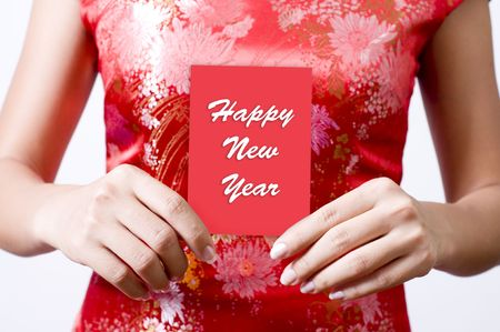 Oriental girl with red Cheongsam holding a red packet wishing you Happy New Year photo