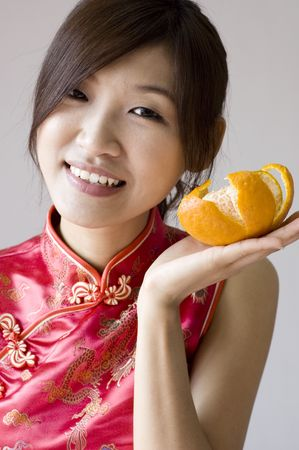 Pretty asian with cheongsam outfit holding a mandarin orange photo