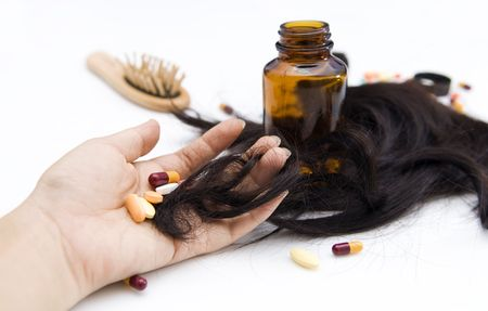 hair problem: Hair loss. Close-up of a hand with pills and loss hair.