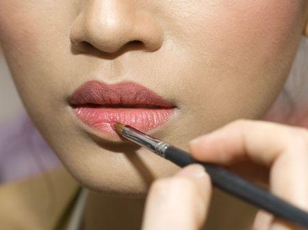 mujer maquillandose: Una joven mujer aplicar maquillaje