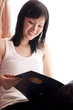 Young Asian woman reading book at home. photo