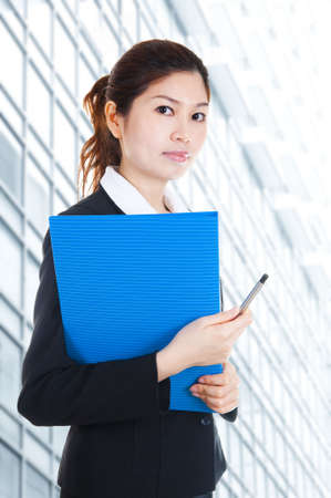 Young Business Women holding file standing in front building block. photo