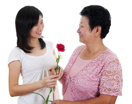 Daughter giving carnation flowers to her mother. Stock Photo