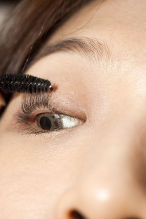 A young woman applying makeup, close-up on eye. photo