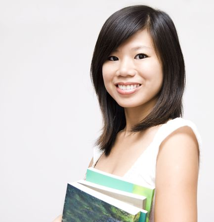 A young Asian girl standing with books.  photo