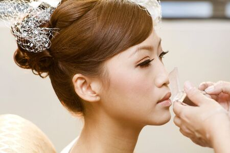 bridal hair: Bridal applying cosmetic with applicator. Make-up treatment.