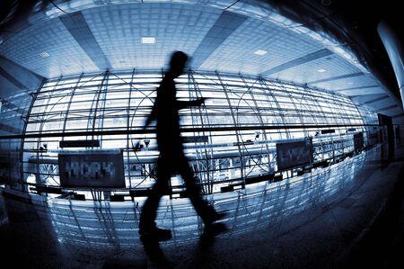 defocussed: People silhouette walking through in modern building, in fish eye view.