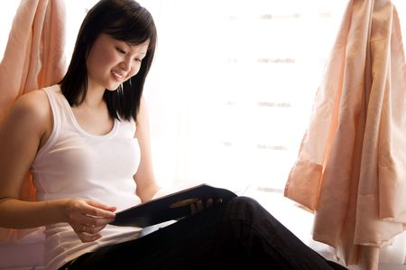 Young Asian woman reading at home. photo
