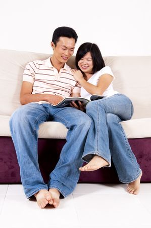 adult magazines: Asian couples sitting on sofa sharing a book. Stock Photo