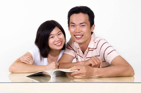 Asian couples sharing a book. photo