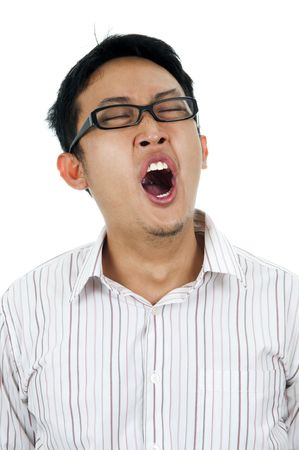 Tired and unshaved young Asian businessman yawning. photo