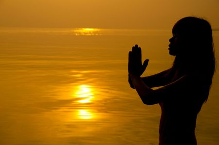 praise and worship: Woman with hands folded at seaside during sunset. Stock Photo