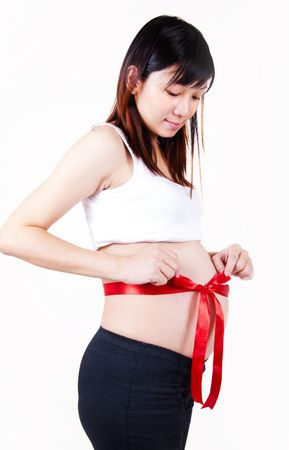 Young Asian pregnant women with red bow tied on her stomach. photo