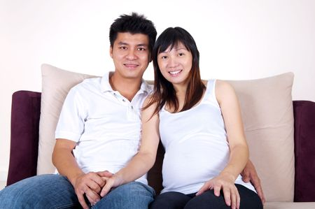 Husband and 8 months pregnant wife sitting on sofa. photo