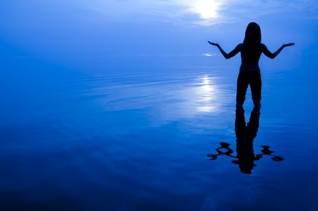 healing hands: Abstract women silhouette in the sea looking at sun with arms open.