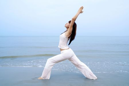Woman practising Yoga (Warrior Position) on the beach. photo