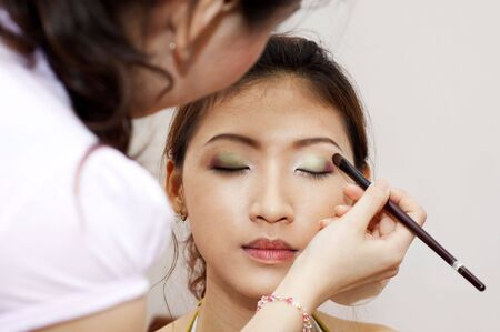 makeover: Woman applying cosmetic with applicator. Make-up treatment. Stock Photo