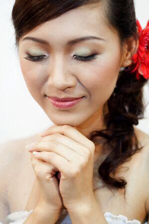 Beautiful Asian bride is praying. photo