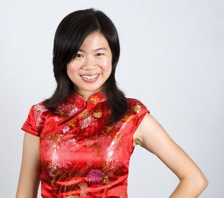Oriental woman in red Cheongsam. Cheongsam also known in English as a mandarin gown, is  formal wear for important occasions. Red is lucky color of Chinese, red cheongsam usually wear by during new year day or wedding. photo