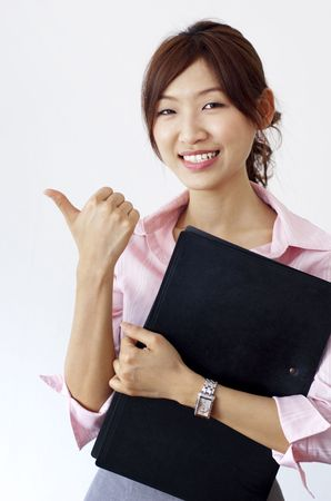 An Asian girl giving thumbs up sign and holding a file. photo