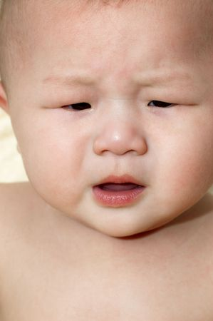 An upset Asian baby boy is crying. photo