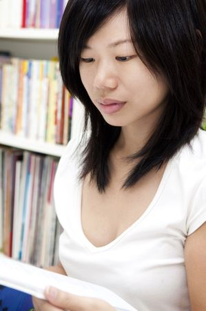 Young Asian young female student studies in the library. photo