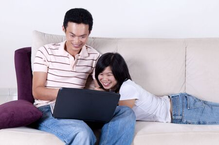 Asian young couple sharing informations from internet. photo