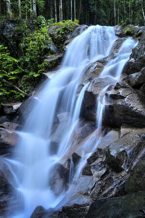 Natural waterfall at tropical rainforest Malaysia in a morning. photo