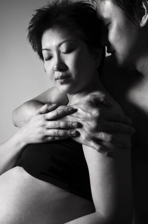 Asian couple, 8 months pregnant women in low key. photo
