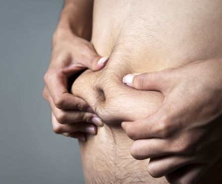 nude man: A man pinches his body fat.