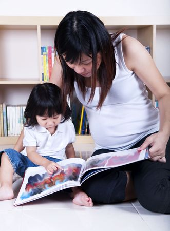 Pregnant mother and her daughter reading together. photo