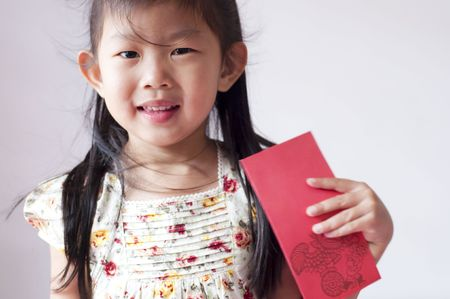 Happy chinese girl holding a chinese red envolope. Red envelope or red packet is a monetary gift which is given during holidays or special occasions, such as weddings or Lunar New Year. Stock Photo - 6117674
