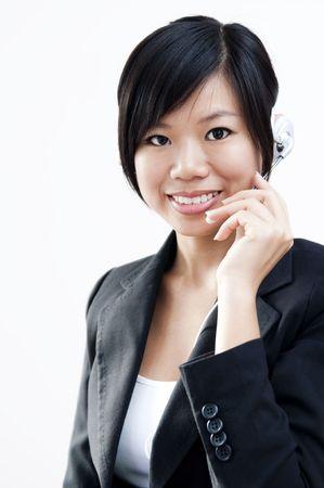 hands free phone: Representante de cliente amistoso con el kit manos libres port�til sonriente durante una conversaci�n telef�nica.