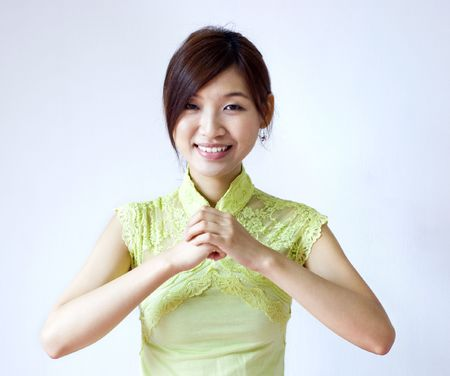 Oriental girl with traditional Cheongsam suit wishing you a happy Chinese New Year photo