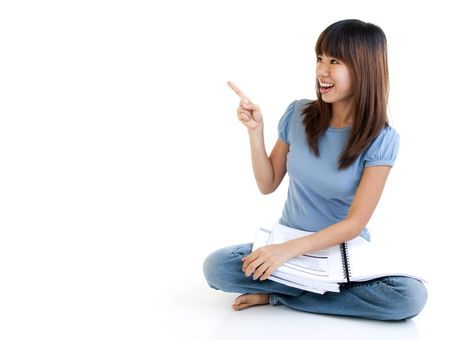 Asian student sitting on floor, pointing to empty space, ready for text. Stock Photo - 6360850
