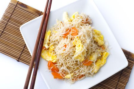 Asian fried rice vermicelli with eggs and carrot. Serve with chopsticks. photo