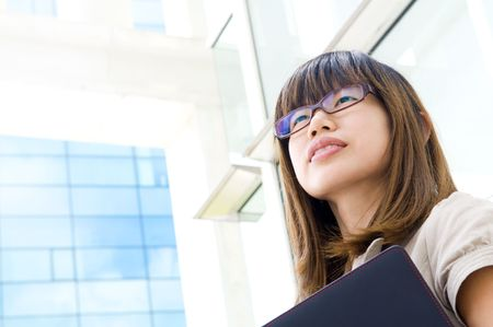 A young Asian woman looking far away to bright light in front of a modern office building, with diary on hand. photo