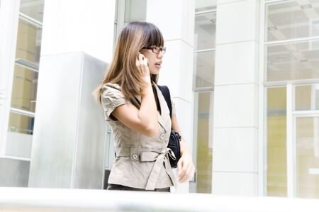 Asian Businesswoman walking on street passing by an office building, motion blurred. photo