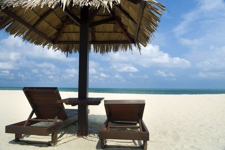 Tropical beach with hut and chairs. photo