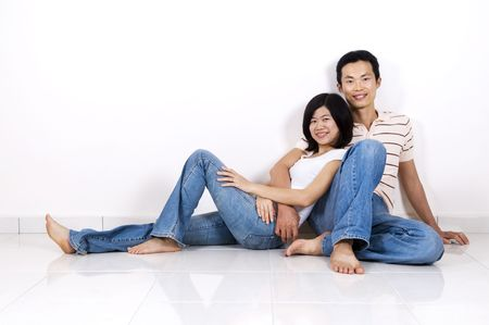 Young Asian adult couple sitting together on tiles floor in home smiling. photo