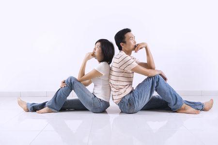 frau sitzt am boden: Young Asian adult Couple sitting together auf Fliesen Fu�boden im Haus nachgedacht.