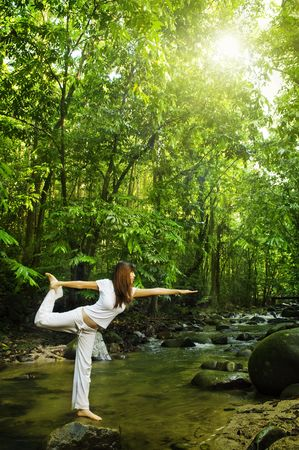 stretching: Coventículos femeninos de equilibrio en el bosque tropical de la naturaleza en una mañana.